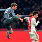 Bayern Munich's Thomas Mueller launches himself towards Ajax's Nicolas Tagliafico