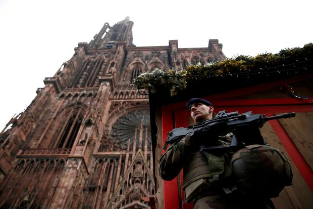 A French soldier stands guard near a closed wooden barrack shop at the traditional Christkindelsmaerik (Christ Child market) in front of the Cathedral the day after a shooting in Strasbourg, France, December 12, 2018. REUTERS/Christian Hartmann
