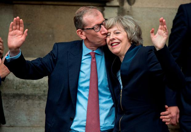 Theresa May gets a kiss from her husband Philip John May. Photo: Getty