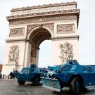 Police armored personnel carriers are parked in front of the Arc de Triomphe, Saturday. Prized Paris monuments and normally bustling shopping meccas locked down and tens of thousands of police took position around France. Photo: AP