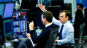 Traders work at their desks whilst screens show market data at CMC Markets in London. Photo: Reuters