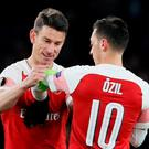 Arsenal's Laurent Koscielny gives the captains armband to Mesut Ozil REUTERS/David Klein