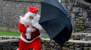 Jolly brolly: Santa battles the elements to see all the children at Murrisk community centre near Westport, Co Mayo. Photo: Paul Mealey