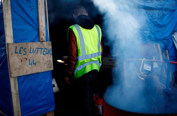 A protester wearing a yellow vest stands inside a makeshift shelter at a roundabout near the Nantes Atlantique Airport as the