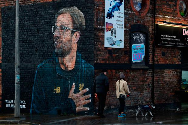 A couple with a dog walk past a recently created mural of Liverpool manager Jurgen Klopp by street artist 'Akse' near Anfield. Photo: Getty Images