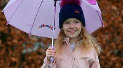 Sheltered: Olivia Gray (8) plays in the rain in Rathcoole, Co Dublin. Photo: Damien Eagers