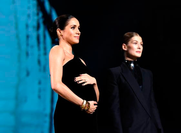 Meghan Markle cradles her baby bump in a chic asymmetric gown for surprise appearance at British Fashion Awards