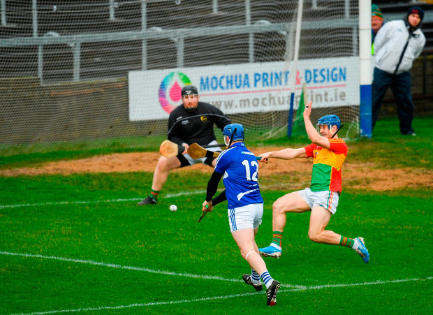 Stephen Maher of Laois scores his side's first goal despite the attention of Micheal Doyle of Carlow. Photo by Eóin Noonan/Sportsfile