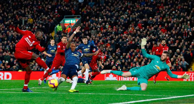 Liverpool's Naby Keita shoots at goal as Manchester United's Ashley Young attempts to block and David de Gea attempts to save. Photo: REUTERS/Phil Noble