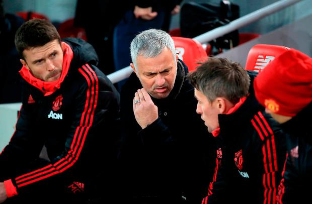 A frustrated Jose Mourinho in conversation with his assistants at Anfield. Photo: PA