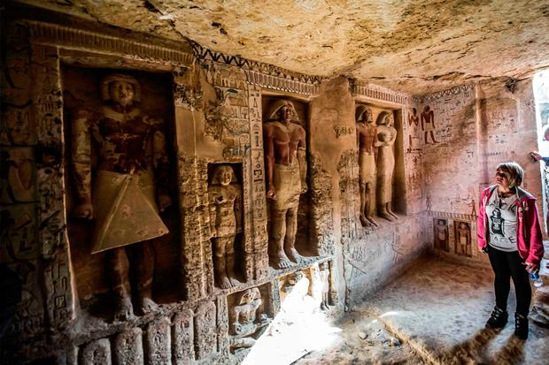 First light: A visitor gazes at the sculpted figures on the walls of the tomb of Wahtye in Saqqara, Egypt. Photo: AFP/Getty Images