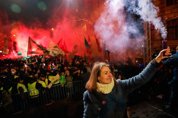 Taking a stand: Vice-chair of the Momentum party Anna Donath holds up a smoke grenade at protests in Budapest. Photo: AP