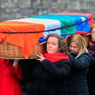Farewell: Councillor Eilis Ryan, wearing a red scarf, among mourners carrying the coffin of Sean Garland at Glasnevin Cemetery, Dublin. Photo: Gareth Chaney, Collins