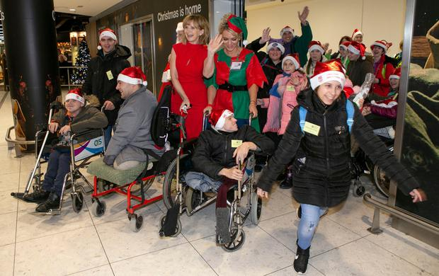 Festive cheer: Sasha Shtepa leads the way as young people from Chernobyl are welcomed by Adi Roche (red dress) and supporters of Chernobyl Children International at Dublin Airport for their annual visit from Belarus. Photo: Kyran O'Brien