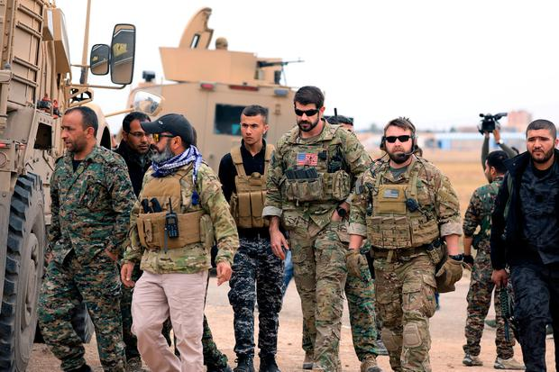 On the move: Syrian Democratic Forces and US troops are seen during a patrol near the Turkish border in Hasakah, Syria. Photo: REUTERS/Rodi Said