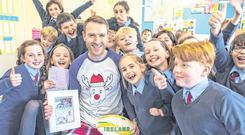 PJ day: Shane McCarthy wearing Peter O'Mahony's pyjamas with pupils from his school. Photo: Michael Sweeney/Provision