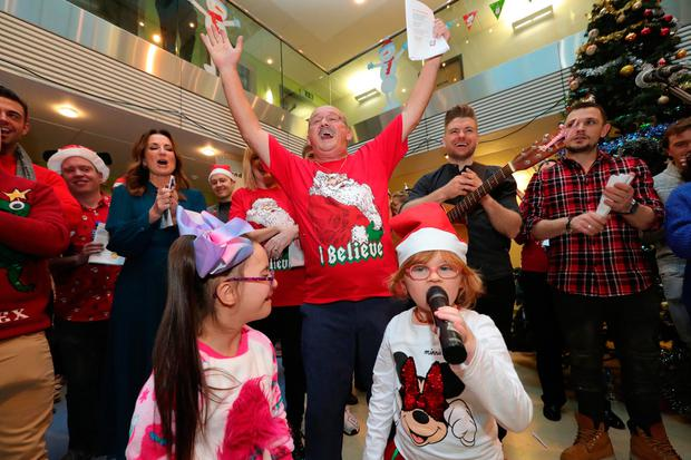 Brendan O'Carroll leads the singing at Crumlin Children's Hospital with Faith Fay (6) and Zoe Longergan (7)