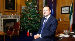 An Taoiseach, a big fan of Christmas decorations, relaxes beside the Christmas tree in his office. Photo: David Conachy