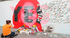 Referendum: A woman kneeling in front of a mural of Savita Halappanavar in Dublin as votes were counted in the referendum on the Eighth Amendment in May. Photo: Niall Carson/PA Wire