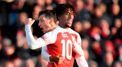 Alex Iwobi celebrates with Mesut Ozil after scoring Arsenal's third goal against Burnley at the Emirates Stadium. Photo by Shaun Botterill/Getty Images