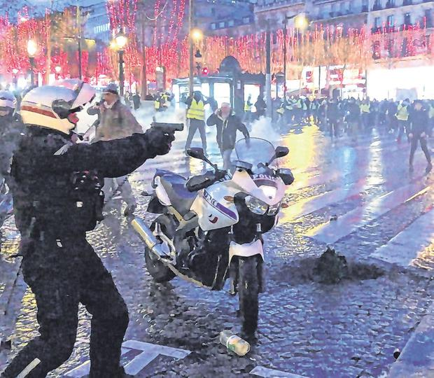Threat: A policeman brandishes his gun at protesters in Paris. Photo: Clement Lanot via AP
