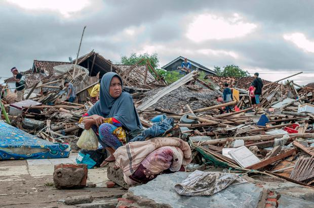 A tsunami survivor sits on a pice of debris as she salvages items from the location of her house in Sumur, Indonesia, Monday, Dec. 24, 2018. (AP Photo/Fauzy Chaniago)