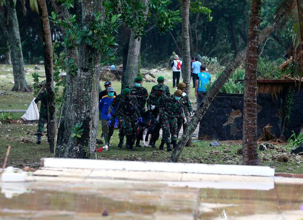 Indonesian soldiers carry the bodies of tsunami victims at Tanjung Lesung beach, Indonesia, Monday, Dec. 24, 2018. (AP Photo/Achmad Ibrahim)