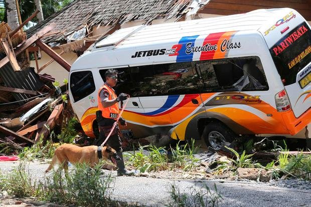 A police officer carries his K9 unit search dog as they continue to search for victims following a tsunami around a beach hotel in Tanjung Lesung, Indonesia, Monday, Dec. 24, 2018. (AP Photo/Tatan Syuflana)