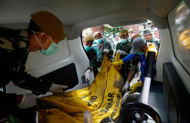 Indonesian soldiers load the body of a tsunami victim into an ambulance at Tanjung Lesung beach resort, Indonesia, Monday, Dec. 24, 2018. (AP Photo/Achmad Ibrahim)