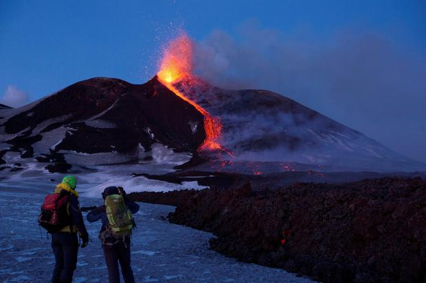 FILE PHOTO: Volcano guides stand in front of Italy's Mount Etna, Europe's tallest and most active volcano, as it spews lava during an eruption on the southern island of Sicily, Italy February 28, 2017. REUTERS/Antonio Parrinello/File Photo