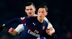 Mesut Ozil of Arsenal is challenged by Pascal Grob of Brighton & Hove Albion. Photo: Getty