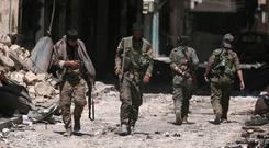 Syria Democratic Forces (SDF) fighters walk on the rubble of damaged shops and buildings in the city of Manbij, in Aleppo Governorate, Syria, August 10, 2016. REUTERS/Rodi Said/File Photo