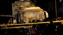 Security forces stand near a tourist bus after a roadside bomb in an area near the Giza Pyramids in Cairo, Egypt, (AP Photo/Nariman El-Mofty)