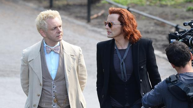 Michael Sheen (white coat) with co-star David Tennant (red hair) as they film a scene from Good Omens (John Stillwell/PA)