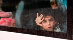 Seeking safety: A Syrian boy looks through the glass window of a bus carrying him and others to the Abu Duhur checkpoint. Photo: Getty Images