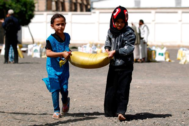 Yemeni children carry food aid distributed by a local charity in Sanaa. Photo: Getty Images