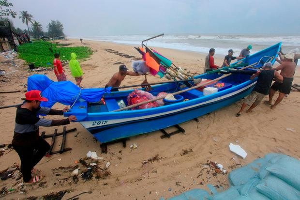 Thai men push a fishing boat off the ocean to a safer location in Songkhla, Thailand in preparation for storm weather conditions on Thursday, Jan. 3, 2019. (AP Photo/Sumeth Panpetch)