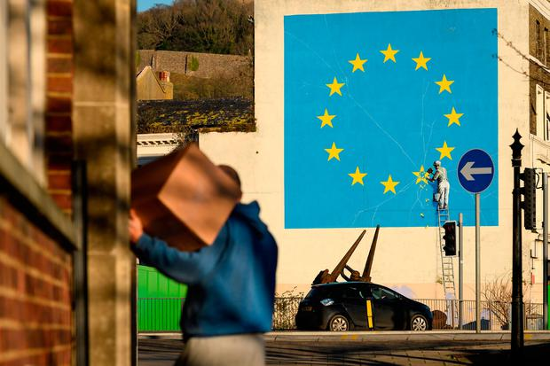 Statement: A painting depicting a workman chipping away at a star on the EU flag by artist Banksy in the southern England port town of Dover. Photo: Getty
