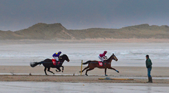 A man looks on as runners and riders participate in the 50th anniversary of the Christmas beach races in Ballyheigue Photo: REUTERS/Clodagh Kilcoyne