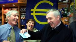 The then Taoiseach, Bertie Ahern, jokes about the new euro currency with Jim O'Neill and his wife Marian, of O'Neill's newsagents, in January 2002. Photo: PA