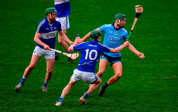 Chris Crummey of Dublin in action against Paddy Purcell and Aaron Dunphy of Laois. Photo by Brendan Moran/Sportsfile