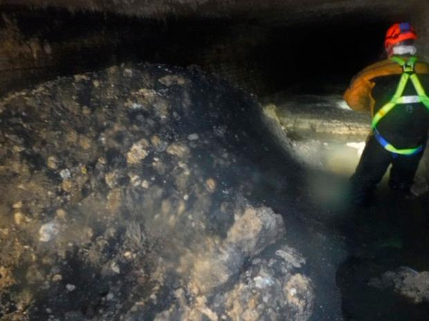Sewage worker inspects a build up of
