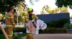 A fire fighter is seen carrying a hazardous material bag into the Korean consulate in Melbourne, Wednesday, Jan. 9, 2019. (James Ross/AAP Image via AP)