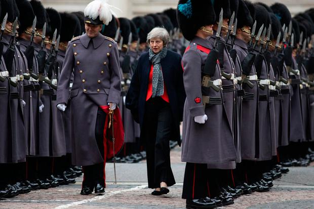 Under fire: Theresa May with British army officer major general Benjamin John Bathurst as Japanese Prime Minister Shinzo Abe receives a military guard of honour in London. Photo: Getty Images