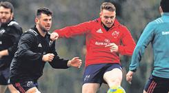 Rory Scannell is tackled by Conor Oliver, left, as the Munster players swopped a round ball for an oval ball in training this week. Photo: Piaras Ó Mídheach/Sportsfile