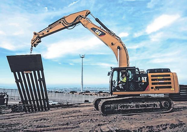 Works: A construction crew replaces a US-Mexico border fence as seen from Tijuana. Photo: GUILLERMO ARIAS/AFP/Getty Images