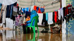 A Syrian refugee hangs clothes to dry at a flooded refugee camp in the town of Bar Elias, in the Bekaa Valley, Lebanon. Photo: Bilal Hussein/AP