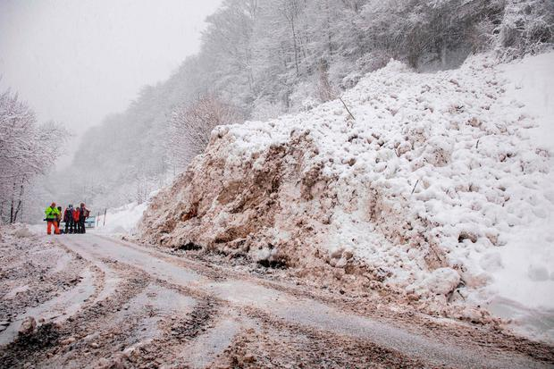 Workers remove snow from a road after an avalanche in Marktschellenberg, southern Germany, on January 9, 2019. (Photo by Bernd März / dpa / AFP) / Germany OUTBERND MARZ/AFP/Getty Images