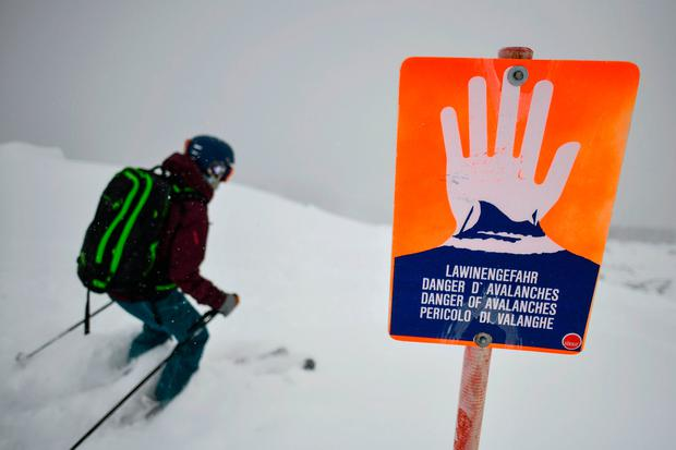 A backcountry skier passes an avalanche warning sign at the sidecountry boundary of a ski resort on January 10, 2019 in Lermoos, Austria. (Photo by Philipp Guelland/Getty Images)