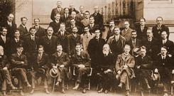 First row: Laurence Ginnell, Michael Collins, Cathal Brugha, Arthur Griffith, Eamon de Valera, Count Plunkett, Eoin Mac Neill, William Cosgrave, Ernest Blythe. Second row: P Maloney, Terence Mac Swiney, Richard Mulcahy, Joseph O'Doherty, Sean O'Mahony, James Dolan, Joseph MacGuinness, Patrick O'Keeffe, Michael Staines, Joseph MacGrath, Dr Bryan Cusack, Liam de Roiste, Michael Colivet, Fr Michael O'Flanagan (not a member of the Dail, but chaplain to it). Third row: Peter Ward, Alexander McCabe, Desmond FitzGerald, Joseph Sweeney, Dr Hayes, Con Collins, Padraic O Maillie, James O'Mara, Brian O'Higgins, Seamus Burke, Kevin O'Higgins. Fourth row: Joseph Mac Donagh, Sean MacEntee. Fifth row: Piaras Beaslai, Richard Barton, Paul Galligan. Sixth row: Philip Shanahan, Sean Etchingham